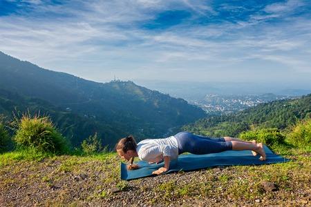 ashtanga: Beautiful sporty fit woman practices Ashtanga Vinyasa yoga pose outdoors in mountains. Himachal Pradesh, India Stock Photo