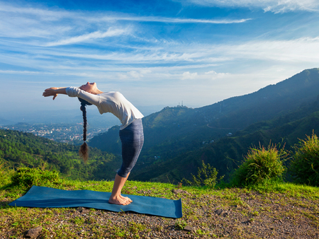 hasta: Young sporty fit man doing yoga Sun salutation Surya Namaskar pose Hasta Uttanasana outdoors in mountains Stock Photo