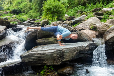 pada: Young sporty fit woman doing yoga asana Eka Pada Koundinyasana 1 at tropical waterfall