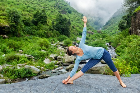 asana: Woman doing Ashtanga Vinyasa yoga asana Utthita trikonasana - extended triangle pose outdoors at waterfall in Himalayas