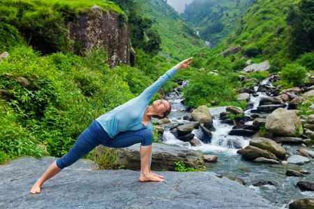 side angle pose: Sporty fit woman practices yoga asana Utthita Parsvakonasana -  extended side angle pose outdoors at water Stock Photo