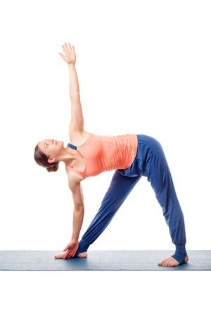 yogic: Beautiful sporty fit woman practices yoga asana utthita trikonasana - extended triangle pose isolated on white background