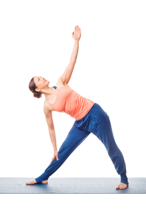 trikonasana: Beautiful sporty fit woman practices yoga asana utthita trikonasana - extended triangle pose beginner variation isolated on white background