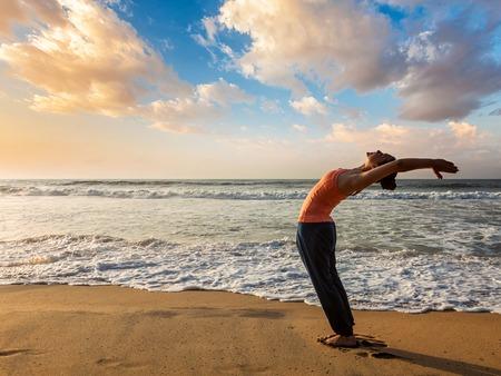 namaskar: Young sporty fit woman doing yoga Sun salutation Surya Namaskar pose Hasta Uttanasana on tropical beach on sunset Stock Photo