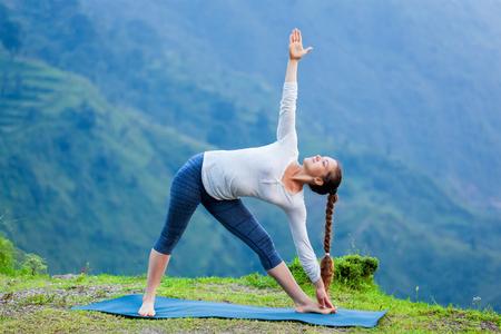 Mujer que hace yoga Ashtanga Vinyasa asana Utthita trikonasana - extended triángulo plantean al aire libre