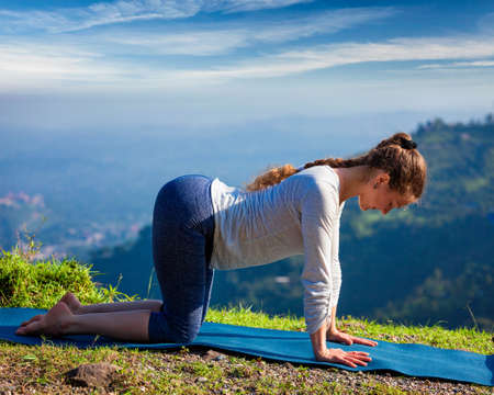asana: Sporty fit woman practices yoga asana bitilasana - cow pose outdoors in mountains Stock Photo