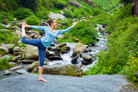 stream: Woman doing yoga asana Natarajasana - Lord of the dance pose outdoors at waterfall in Himalayas
