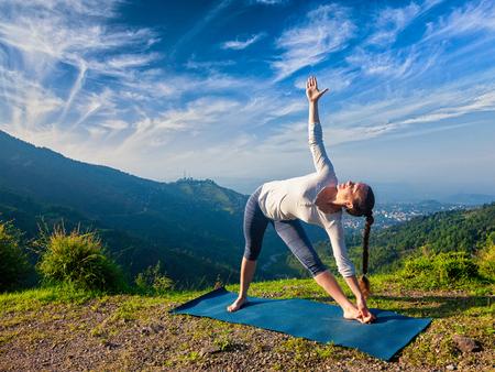 ashtanga: Woman doing Ashtanga Vinyasa yoga asana Utthita trikonasana - extended triangle pose outdoors in mountains in the morning Stock Photo