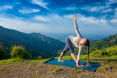 revolved: Woman doing Ashtanga Vinyasa yoga asana Parivrtta trikonasana - revolved triangle pose outdoors in mountains in the morning Stock Photo