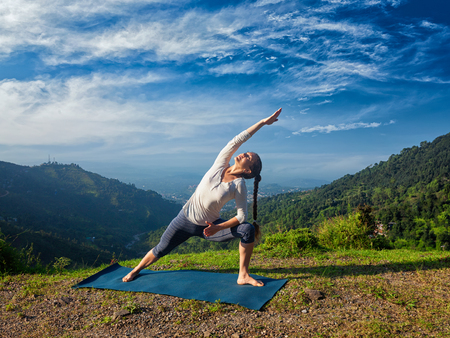 utthita: Sporty fit woman practices yoga asana Utthita Parsvakonasana -  extended side angle pose outdoors in mountains in the  morning