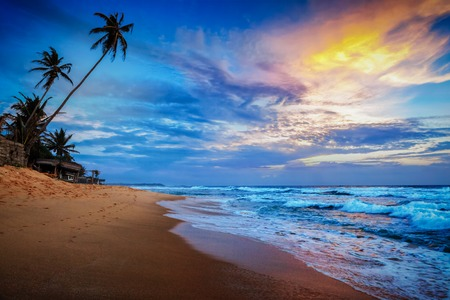 wav: Beach holidays vacation romantic concept background - sunset on tropical beach with dramatic cloud sky. Sri Lanka