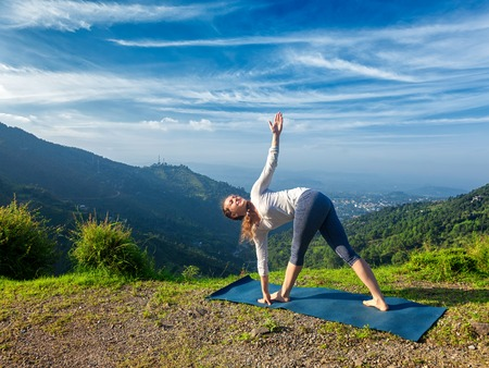 parivrtta: Woman doing Ashtanga Vinyasa yoga asana Parivrtta trikonasana - revolved triangle pose outdoors in mountains in the morning Stock Photo