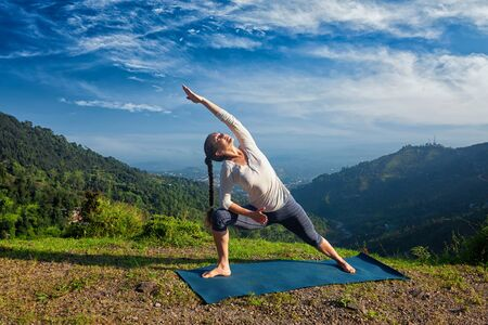 parsvakonasana: Sporty fit woman practices yoga asana Utthita Parsvakonasana -  extended side angle pose outdoors in mountains in the  morning