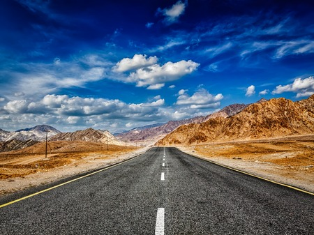 plains indian: Travel forward journey concept - road in mountains Himalayas and dramatic clouds on blue sky. Ladakh, Jammu and Kashmir, India Stock Photo