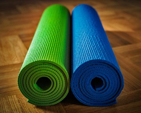Yoga concept background - yoga mats on wooden floor