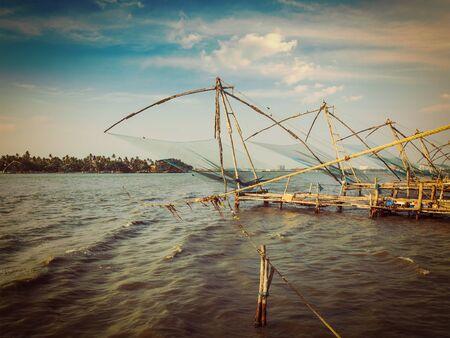 chinese fishing nets: Vintage retro effect filtered hipster style image of Kochi chinese fishnets on sunset. Fort Kochin, Kochi, Kerala, India