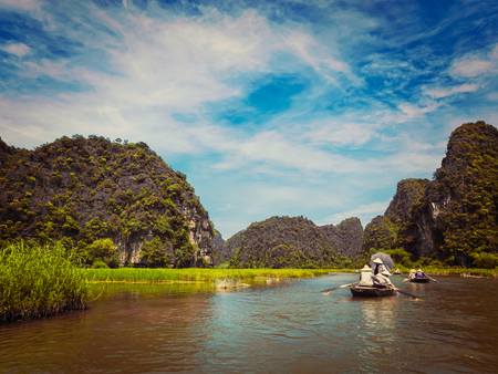 ngo: Vintage retro effect filtered hipster style image of tourists on boats in Tam Coc-Bich Dong Ngo Dong river in popular tourist destination near Ninh Binh, Vietnam