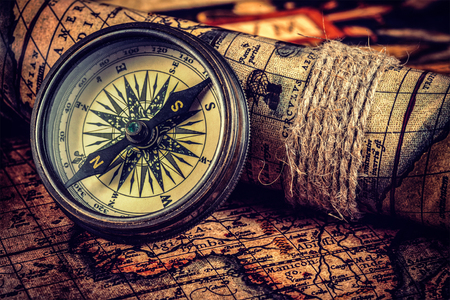 Travel geography navigation concept background - vintage retro effect filtered hipster style image of old vintage retro compass on ancient world map