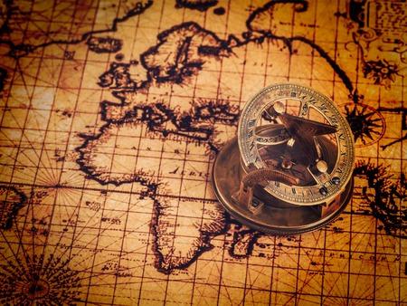 reloj de sol: imagen filtrada efecto estilo retro inconformista de la vendimia del comp�s retro viejo de la vendimia con el reloj de sol en la antigua mapa del mundo - los viajes a la geograf�a del concepto del fondo de navegaci�n