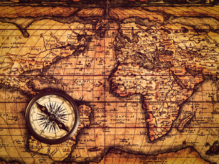 vintage travel: Travel geography navigation concept background - vintage retro effect filtered hipster style image of old vintage retro compass on ancient world map