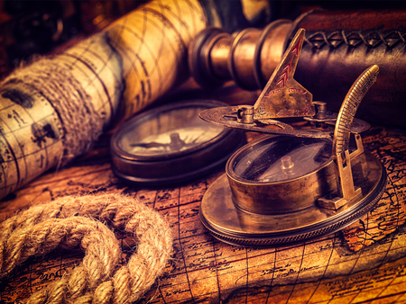 reloj de sol: Travel geography navigation concept background - vintage retro effect filtered hipster style image of old vintage retro compass with sundial, spyglass and rope on ancient world map Foto de archivo
