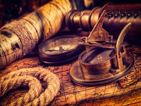 reloj de sol: Viajar geograf�a fondo concepto de navegaci�n - imagen filtrada efecto estilo retro inconformista de la vendimia del comp�s retro viejo de la vendimia con el reloj de sol, el catalejo y cuerda en el antiguo mapa del mundo