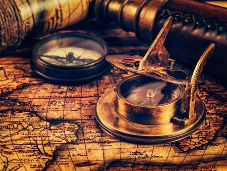 reloj de sol: imagen de la vendimia efecto filtrada estilo inconformista retro de la brújula retro viejo de la vendimia con el reloj de sol y catalejo en el mapa del mundo antiguo - viajar geografía de navegación concepto de fondo. copyspace