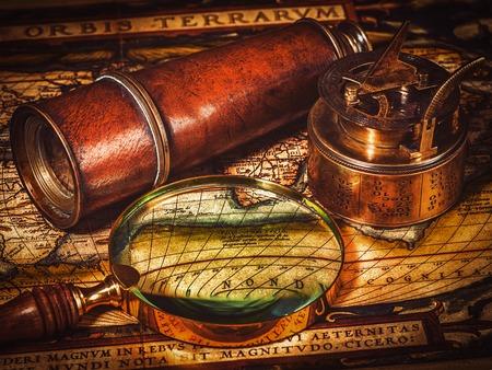 reloj de sol: imagen filtrada efecto estilo retro inconformista de la vendimia del comp�s retro viejo de la vendimia con el reloj de sol, el catalejo y una lupa sobre el antiguo mapa del mundo - los viajes a la geograf�a del concepto del fondo de navegaci�n