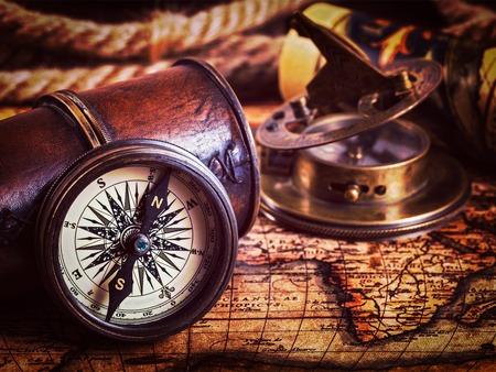 reloj de sol: Viajar geografía fondo concepto de navegación - imagen filtrada efecto estilo retro inconformista de la vendimia del compás retro viejo de la vendimia con el reloj de sol, el catalejo y cuerda en el antiguo mapa del mundo