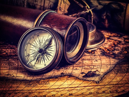 sun dial: Travel geography navigation concept background - vintage retro effect filtered hipster style image of old vintage retro compass with sundial, spyglass and rope on ancient world map Stock Photo