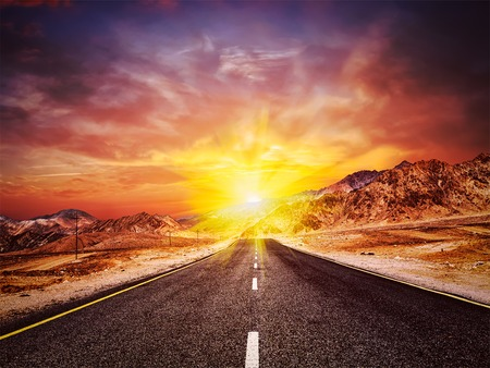 vintage travel: Travel forward concept background - vintage retro effect filtered hipster style image of road in Himalayas with mountains and dramatic clouds on sunset. Ladakh, Jammu and Kashmir, India Stock Photo