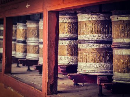 gompa: Vintage retro effect filtered hipster style image of Buddhist prayer wheels in Hemis gompa (Tibetan buddhist monstery). Ladakh, India Stock Photo