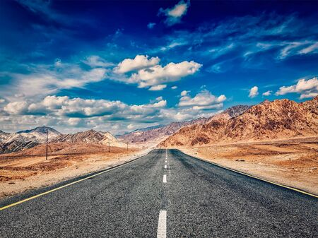 plains indian: Vintage retro effect filtered hipster style image of road in mountains Himalayas and dramatic clouds on blue sky. Ladakh, Jammu and Kashmir, India