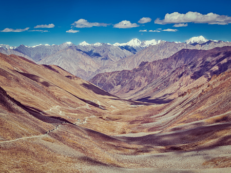 twisty: Vintage retro effect filtered hipster style image of  Karakoram range and road in valley  from Kardung La - the highest motorable pass in the world (5602 m). Ladakh, India Stock Photo