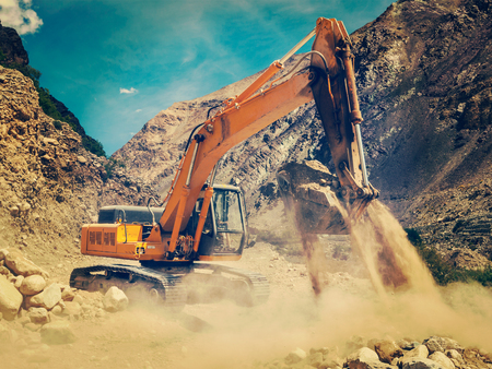 power shovel: Vintage retro effect filtered hipster style image of excavator doing road construction in Himalayas. Ladakh, Jammu and Kashmir, India Stock Photo