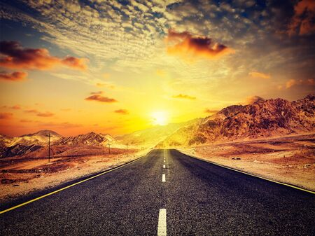 plains indian: Travel forward concept background - vintage retro effect filtered hipster style image of road in Himalayas with mountains and dramatic clouds on sunset. Ladakh, Jammu and Kashmir, India Stock Photo
