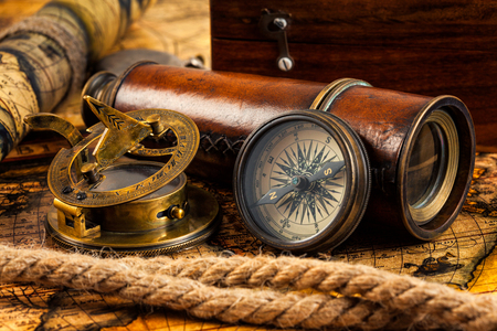 reloj de sol: Travel geography navigation concept background - old vintage retro compass with sundial, spyglass and rope on ancient world map