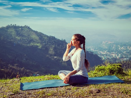 Vintage retro effect hipster style image of woman practices pranayama yoga breath control in lotus pose padmasana outdoors in Himalayas in the morning on sunrise. Himachal Pradesh, India