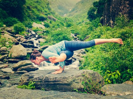 pada: Vintage retro effect hipster style image of sporty fit woman doing yoga asana Eka Pada Koundinyasana 1 at tropical waterfall