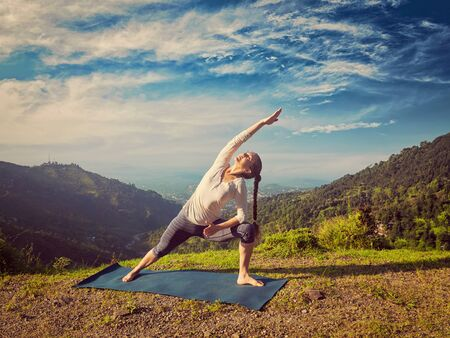 utthita: Vintage retro effect hipster style image of sporty fit woman practices yoga asana Utthita Parsvakonasana -  extended side angle pose outdoors in mountains in the  morning