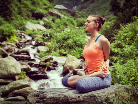 bound woman: Vintage retro effect hipster style image of sporty fit woman doing yoga - meditating in Baddha Padmasana (Bound Lotus Pose) outdoors at tropical waterfall Stock Photo