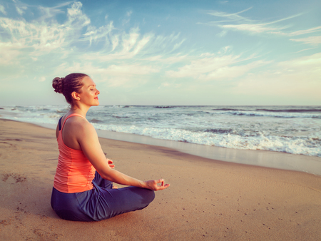 baddha: Vintage retro effect hipster style image of woman doing yoga - meditating and relaxing in Padmasana Lotus Pose) with chin mudra outdoors at tropical beach on sunset
