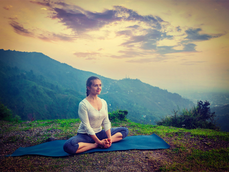baddha: Vintage retro effect hipster style image of sporty fit woman practices yoga asana Baddha Konasana - bound angle pose outdoors in HImalayas mountains on sunset. Himachal Pradesh, India Stock Photo