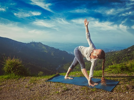revolved: Vintage retro effect hipster style image of woman doing Ashtanga Vinyasa yoga asana Parivrtta trikonasana - revolved triangle pose outdoors in mountains in the morning