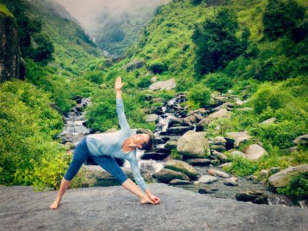trikonasana: Vintage retro effect hipster style image of woman doing Ashtanga Vinyasa yoga asana Utthita trikonasana - extended triangle pose outdoors at waterfall in Himalayas