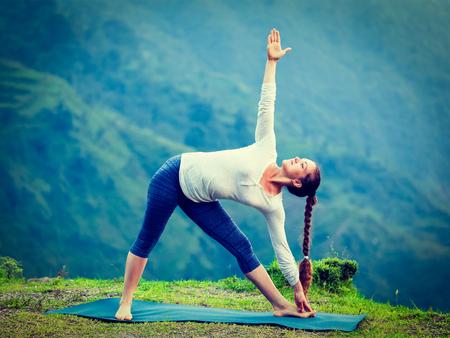 ashtanga: Vintage retro effect hipster style image of woman doing Ashtanga Vinyasa yoga asana Utthita trikonasana - extended triangle pose outdoors Stock Photo