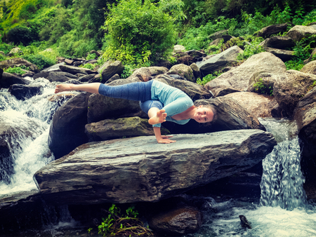 eka: Vintage retro effect hipster style image of sporty fit woman doing yoga asana Eka Pada Koundinyasana 1 at tropical waterfall