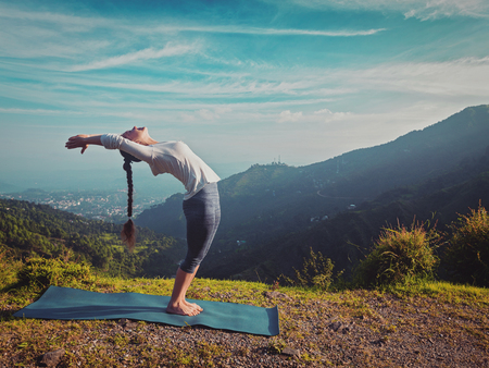 hasta: Vintage retro effect hipster style image of young sporty fit man doing yoga Sun salutation Surya Namaskar pose Hasta Uttanasana outdoors in mountains