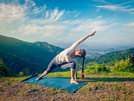 parsvakonasana: Vintage retro effect hipster style image of sporty fit woman practices yoga asana Utthita Parsvakonasana -  extended side angle pose outdoors in mountains in the  morning