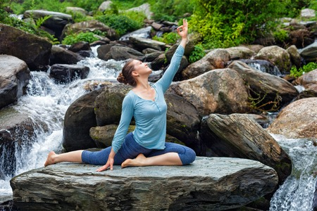 eka: Yoga outdoors - young sporty fit woman doing stretching yoga asana Eka pada rajakapotasana - one-legged king pigeon pose at tropical waterfall Stock Photo